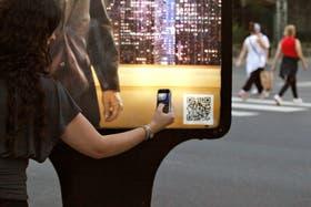 Una mujer levanta un código QR de una publicidad en la vía pública