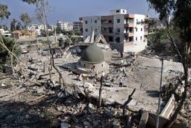 Un grupo de libaneses camina sobre los escombros a los que fue reducido un centro religioso atacado por la aviación israelí, en la ciudad de Sidón