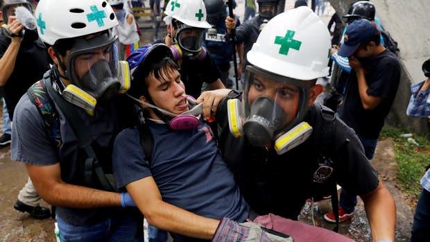 Miembro de primeros auxilios ayudan a un manifestante herido