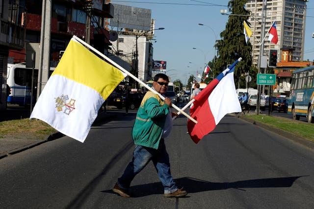 En Temuco, un hombre lleva la bandera del Vaticano y chilena
