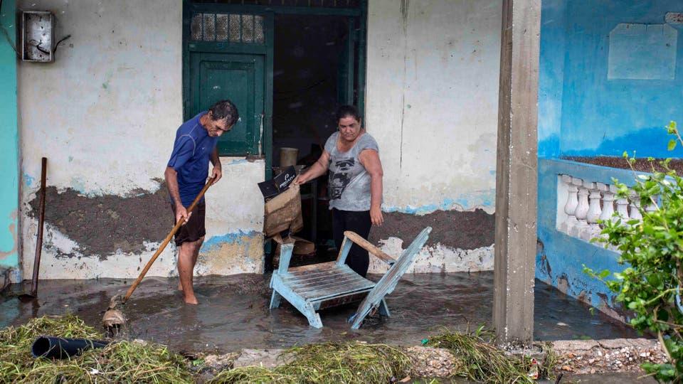 Residentes de Caibarien limpian su casa inundada. Foto: AP / Desmond Boylan