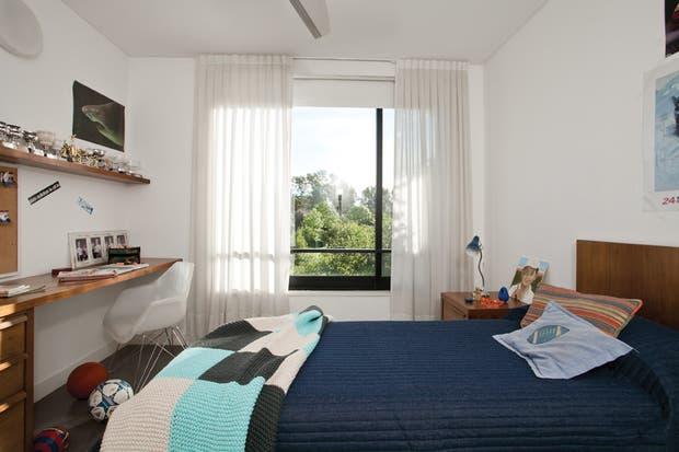El dormitorio del varón, con la evidencia de su afición por los deportes. La cama es otra creación de la dueña de casa vestida con un acolchado de jean matelasé (Home Harmony). En el escritorio, silla de estructura metálica cromada (Manifesto)..
