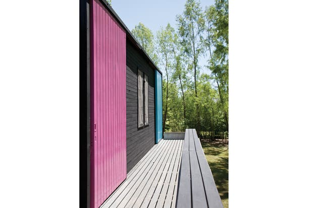 En lugar de tener una baranda, el deck sube y se transforma en un largo banco para sentarse a mirar el bosque..