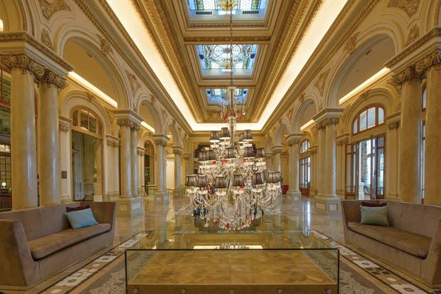 Después: En el antiguo comedor funciona el lobby y la recepción. Los vitraux se pudieron recuperar, pero no así los pisos, que fueron revestidos con mármol..