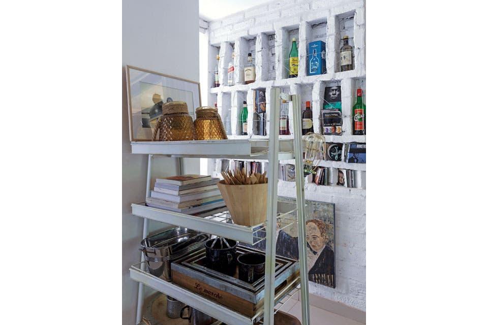 Esta parte de la cocina, que es también paso al lavadero, es parte de la ampliación. La pared de ladrillo se diagramó como una estantería a medida, con recovecos para el bar y los discos. En línea con la columna estructural que divide la cocina, la dueña de casa ubicó un mueble antiguo.  Foto:Living /Daniel Karp