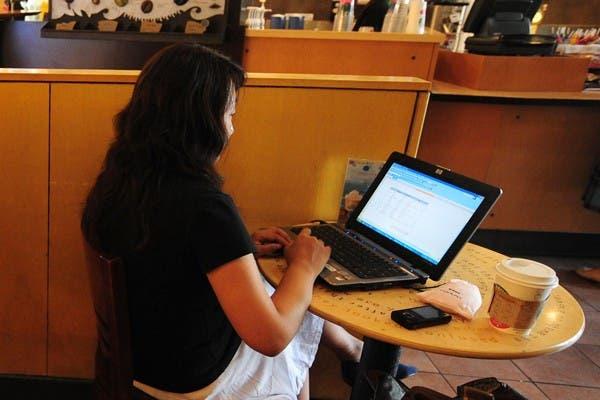 Una mujer trabaja con su computadora portátil en un café