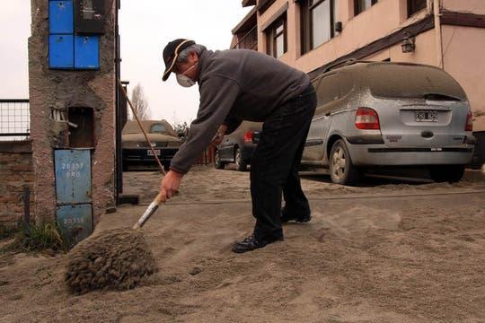 Un hombre quita las cenizas de la puerta de su casa en Bariloche. Foto: DyN