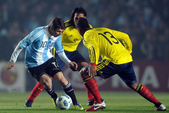 Con los ojos puestos en la pelota Messi avanza frente a Guarin.
