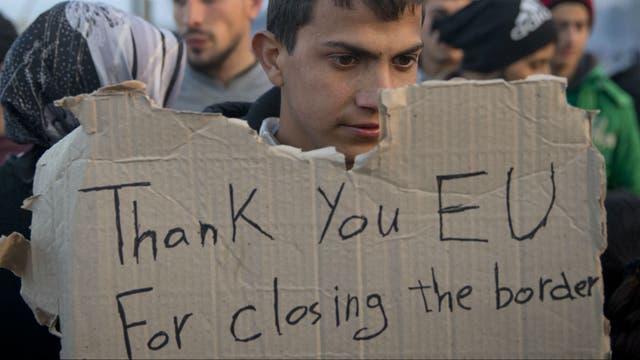 Un refugiados alza un cartel de protesta contra el cierre de fronteras en la UE