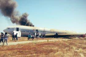 El avión de Asiana Airlines al costado de la pista, incendiado