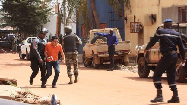 Un agente maliense retira a un rehén del hotel Radisson, que hasta ayer era uno de los más seguros de la capital, Bamako