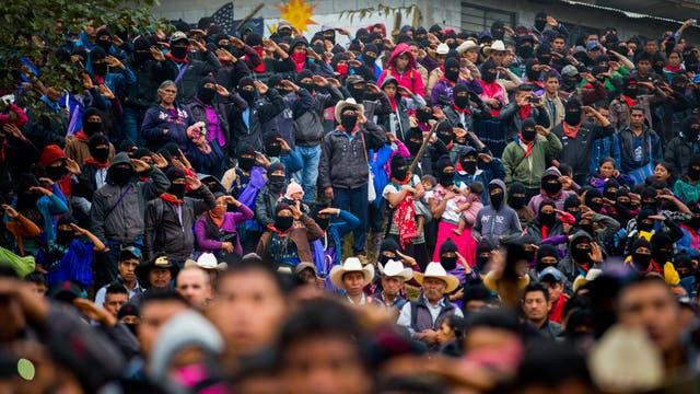 Zapatistas saludan durante la presentación del himno nacional de México en un acto de campaña en el bastión zapatista de Oventic en el estado de Chiapas