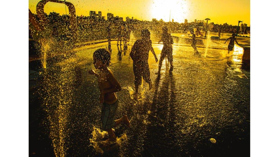 Niños se refrescan para aliviar las altas temperaturas, en el barrio de Nuñez, Buenos Aires, enero 2015.