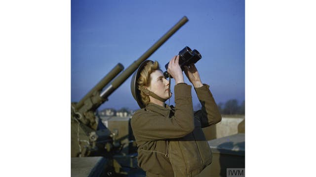 Un miembro del Servicio Territorial Auxiliar (ATS) mira por binoculares junto a un cañón antiaéreo de 3,7 pulgadas, Diciembre 1942.