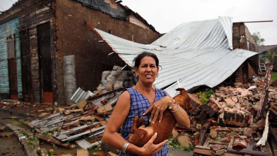 Una mujer posa con su perro frente a su casa destruida por el paso del huracán Irma. Foto: EFE / Alejandro Ernesto