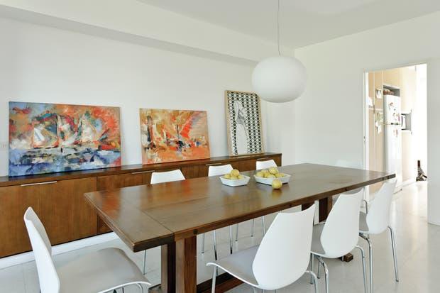 La amplia mesa de comedor de madera de herencia familiar está rodeada por un juego de ocho sillas DC 7A de plástico con estructura de metal cromado (CDI, Centro de Diseño Italiano)..