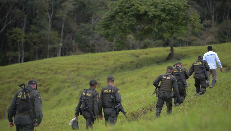La policía de Colombia y un integrante de las FARC patrullan el área donde se lleva a cabo el acto de abandono de las armas de las FARC. Foto: AFP / Raul Arboleda