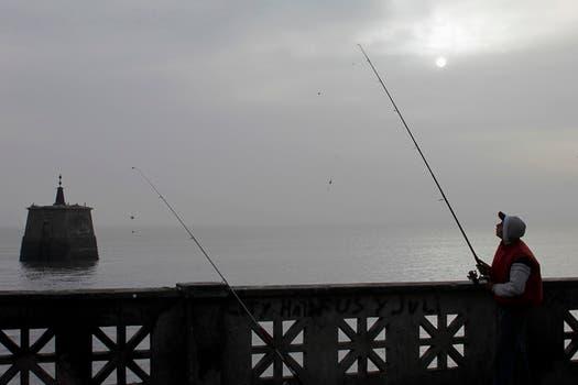Un hombre pesca en el río de La Plata en medio la nube de ceniza. Foto: Reuters