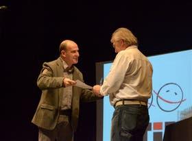 Hector Pressa le entrega a Luis Pescetti la distinción por su trayectoria