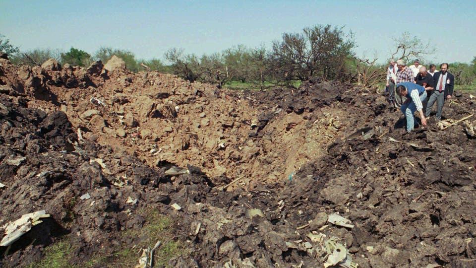 Rescatistas inspeccionan el cráter dejado por el avión al caer