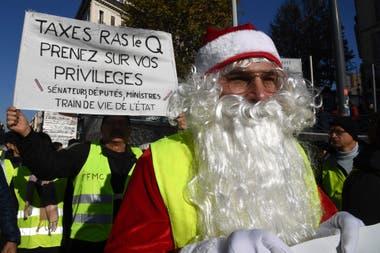 """""""Suficientes impuestos, metete con tus propios privilegios"""", dice el cartel de un Papá Noel con chaleco amarillo"""