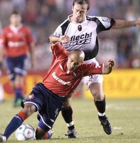 Jorge Martínez, de Independiente, protege la pelota frente al ímpetu de Martín Romagnoli