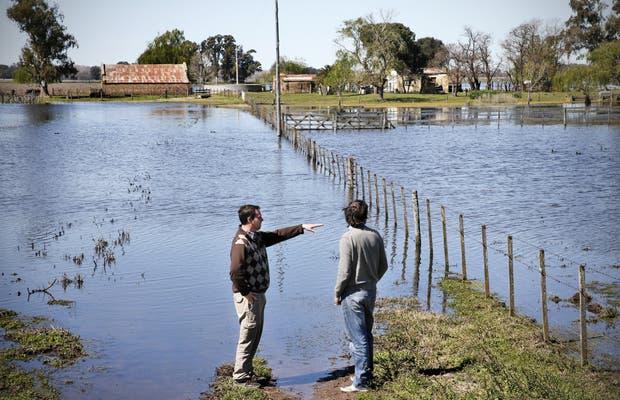 Los productores Pablo Ginestelt y Fernando Reynolds observan el avance de las aguas en el partido bonaerense de Henderson
