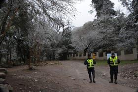 Dos policías custodian el camino de entrada a la villa turistica de la Quebrada de San Lorenzo, en Salta donde el viernes pasado fueron hallados los cuerpos de las turistas francesas
