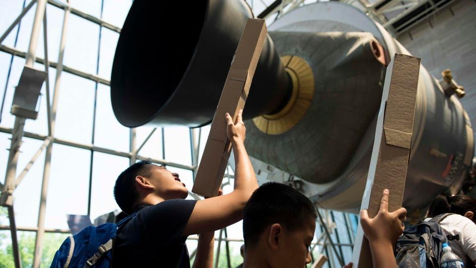 En el museo del aire y del espacio de Smithsonian en Washington, unos jovenes prueba unos telescopios hechos con cartón. Foto: Reuters