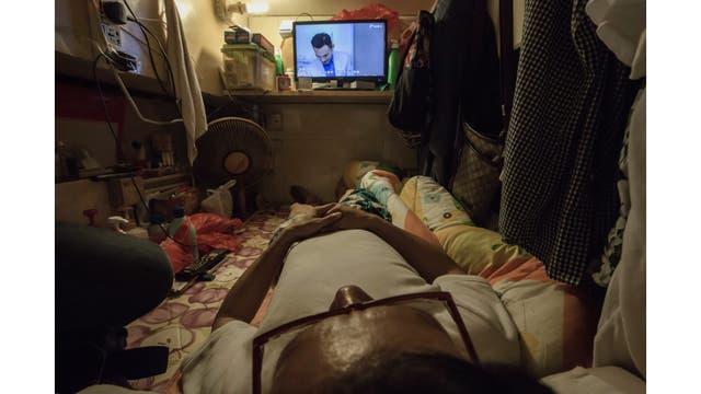 Simon Wong, una hombre desempleado mirando Tv