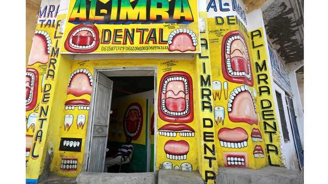El dentista somalí Hassan Ali, de 35 años, se sienta dentro de su clínica dental con murales pintados en las paredes del distrito de Hamarweyne