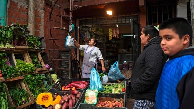 Una mujer pesa verduras en su tienda de la Villa 31 en Buenos Aires, Argentina
