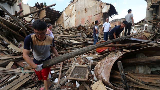 Personas ayudan a remover los escombros de un edificio colapsado por las fuertes lluvias y los vientos que azotaron Lianyuan