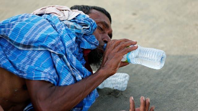 Un refugiado de Rohingya bebe agua después de cruzar la frontera de Bangladesh-Myanmar en barco a través de la bahía de Bengala