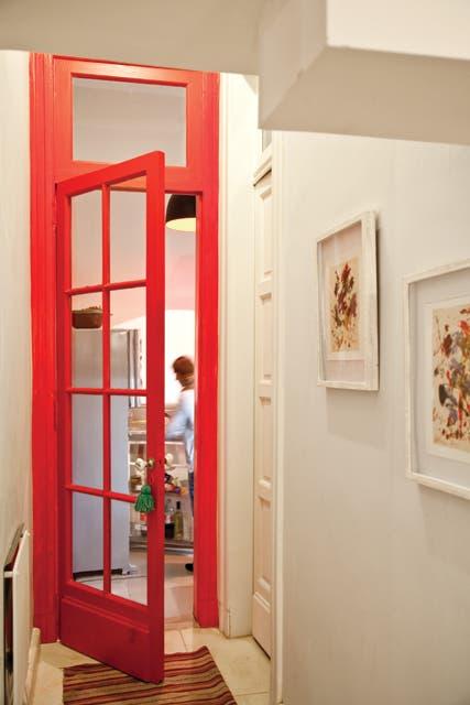 Puerta de vidrio repartido en rojo furioso: un elemento que acentúa la transición y mantiene aislada la cocina. Tiene un picaporte antiguo de Anthropologie..  Foto:Living /Magalí Saberian