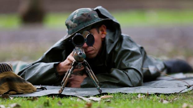 A unos 100 metros de distancia, un tirador con un fusil de precisión hiere levemente a un delincuente que cubría una puerta de acceso a la finca, donde hay un inocente cautivo.
