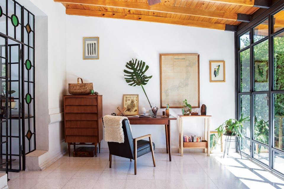 Enfrentada al living, se ubicó el área de trabajo, con cajonera enchapada, escritorio con tapa de fórmica y sillón de estilo escandinavo retapizado con cuero, todo realizado en madera de cedro. A la derecha, una mesa de arrime de fresno e incienso (todo de Becca Estudio). Divino el detalle del mapa .  Foto:Living /Javier Picerno