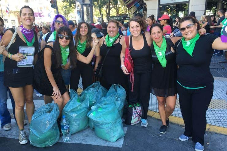 """Activistas de Mumalá van a marchar con pelucas verdes que trajeron en bolsas. """"¡Vamos feministas!"""", gritan al posar para la foto en la 9 de Julio y Av. De Mayo"""