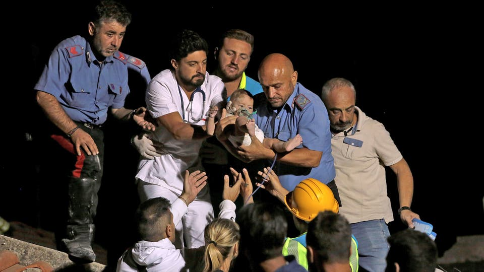 Un doctor es ayudado por bomberos y rescatistas para salvar a un bebé de los escombros
