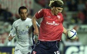 Nicolás Frutos, el hombre gol de los Rojos, se lleva la pelota ante la mirada de Gabriel Ruiz