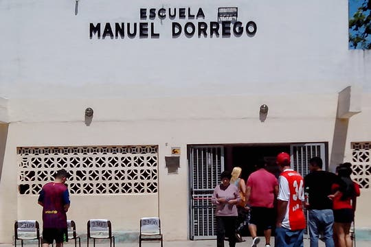 En la entrada de la escuela n° 150 dos jóvenes fiscales del FPV seducen a los votantes. Foto: LA NACION / Iván Ruiz
