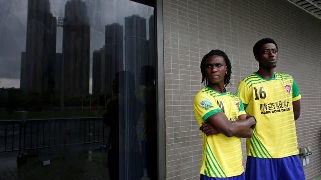 Solomon Nyassi,(izq) de 26 años, de Gambia, miembro de All Black FC, espera antes de unirse a un equipo local para un partido amistoso en Hong Kong, China.