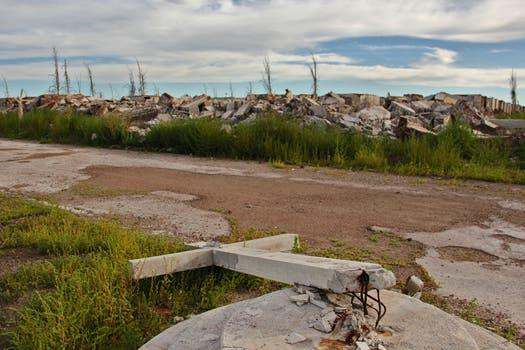La cruz del cementerio de Epecuén, un símbolo del lugar, se quebró por el impacto del agua; detrás, las ruinas de las paredes y los nichos. Foto: LA NACION / Mauricio Giambartolomei