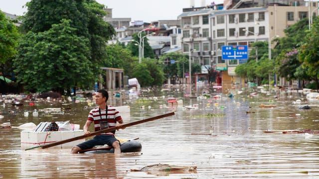 Un hombre con un bote improvisado navega entre la basura de las calles inundadas en Liuzhou