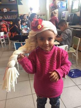 Luz, la primera niña en probar las creaciones de las voluntarias.