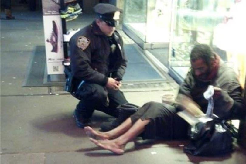 La foto retrata el momento en que el policía Larry de Primo le compra y le poné unas botas a un indigente