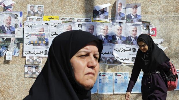 Mujeres caminan junto a carteles electorales en Teherán