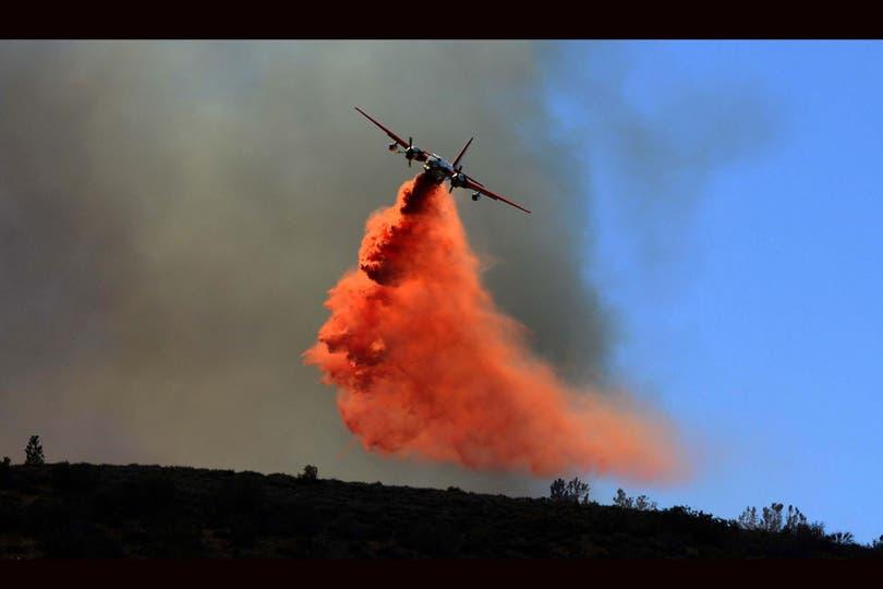 Un avión riega una sustancia retardante del fuego sobre una central eléctrica incendiada en Lancaster. Foto: EFE