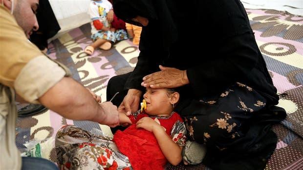 Una chica infectada, al ser tratada por el personal médico de un campamento cerca de Mosul