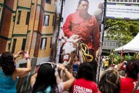 Seguidores de Chávez y turistas toman fotos con un cartel del líder bolivariano detrás
